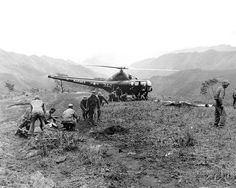 Marines wounded at Kari San Mountain are evacuated via helicopter and flown to hospital in rear areas for treatment. Navy Corpsmen prepare three wounded Marines for evacuation. May 23, 1951.