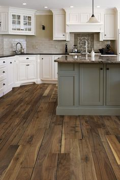 Love the taupe subway tile, white cabinets, gray island and the wide wood plank floor.