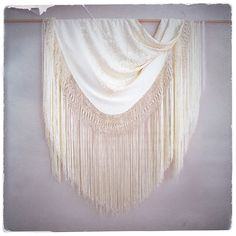 """Truly stunning hand embroidered Spanish shawl with the bohemian brides in mind! Beautiful antique buttery cream color with intricate, heavy floral motif.  Beautiful extra long fishnet fringe that flows so stunningly with every movement! Incredible large size to be worn and or used as a home decoration/throw, or should I say, art piece to be admired.Square Shawl Measurement is 54"""" x 54"""" (not including the fringe)  Shown draped over bamboo..photos are just half of it!..."""
