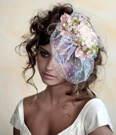 This is A Hat for the Bridal from Michal Negrin Bridal Collection,the hat is made of Vintage inspired handmade headband sewn on a lace base. This headband is decorated with handmade flowers, swarovski crystals and semiprecious stones.