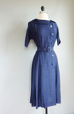 1940s vintage dress. Buttoned up coats and dresses were very popular. This was part of the military inspired fashion since World War 2 took place from 1940-1945.