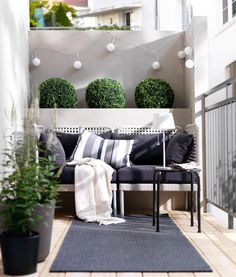 Balcony decorating idea: in black and white with green plants. the cushions and the carpet make the balcony look so cosy almost like a living room I Balkon dekorieren skandinavischer Stil:  Outdoor Teppich, Kissen und grüne Pflanzen