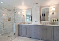Grey vanity, white countertop wall hutch and white framed mirrors