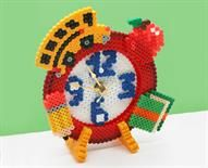 This clock is perfect for school kids to keep on schedule in the morning or while doing homework. This 3-D Perler design stands up and you can easily insert the clock movement.