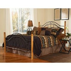 Wood and metal design elements mix perfectly with the Winsloh Bed. Great for a lodge or cottage-themed home this bed features round oak finish hardwood posts with textured black metal panels. Ornate scrolls and clean vertical lines create a casual yet elegant look. You can order the complete bed or just the headboard and it's available in your choice of sizes. Complete bed option includes headboard footboard and bolt-on frame. Headboard only opti