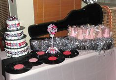 Rock Star Baby Shower - Old records to decorate the tables and divide the diaper cake. Guitar Rice Krispie treats using a guitar cookie cutter and my brother's guitar case with styrofoam hidden in the bottom to display them.