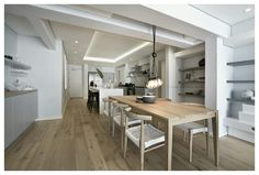 FourOnC Cape Town. Interiors by Del Fante Design Minimalist Oak dining table with horn chairs and cluster bulb pendant