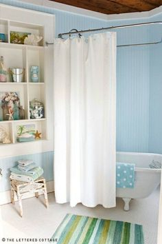 This bathroom takes you to the beach! It is a beautiful cottage style oceanic spa getaway. The walls are painted in a lovely shade of blue. The simple white shower curtain is the perfect choice for this blue painted cozy bathroom. Featured on Completely Coastal along with other blue painted interior rooms. Beach Cottage Style, Beach Cottage Decor, Coastal Cottage, Coastal Style, Coastal Living, Coastal Decor, Blue Painted Walls, Beach Bathrooms, Coastal Bathrooms