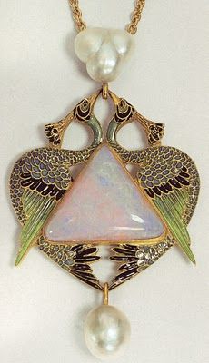 René Lalique c.1901. Pendant in the form of two confronted peacocks standing on the flat edge of a trian-gular cabochon opal, from the base of which a baroque pearl is suspended. The peacocks are formed with cloisonné enameling in light shades of blue and green with dark blue and white wing feathers. Tail feathers terminate in openwork stylized 'eyes' of diamonds and blue enamel.