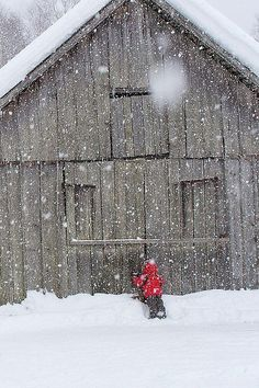 Old barn during snowfall with small figure in red.