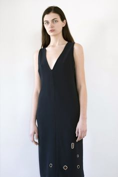 Shift Dress with V shaped Neckline and grommets at front. Classic silhouette updated with silver tone Grommet embellishment 100% polyester Crepe...