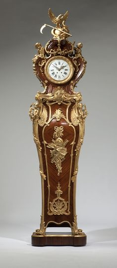 A Regence style ormolu-mounted kingwood parquetry regulator ::  Last quarter 19th century, Paris, one mount removed to reveal stamp of bronzier 'H. Kahn',  the twin train movement stamped ''3796 / 64'', the case in the manner of Charles Cressent, the figural cresting allegorical of victory over time, depicting an eagle atop an orb with a scythe and a snake, surmounting a shaped waisted case enclosing a white enameled dial with Roman hours and Arabic minutes, flanked by two cherubs, one…