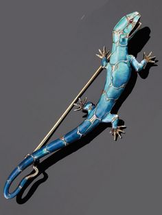 AN ART NOUVEAU SILVER AND ENAMEL LIZARD BROOCH, BY MEYLE & MAYER. Realistically modelled with a red paste eye, maker's mark, 9.5cm. long, circa 1900.