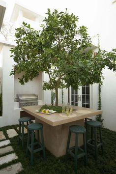 table en béton avec pommier au milieu dans le jardin de style méditerranéen