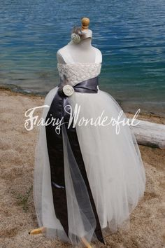 Minus the weird feathers   The Brenna  An ivory  rosette tutu dress with gray speckled feather accents. $124.95, via Etsy.