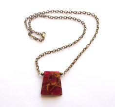 Halsband i brons med röd mosaiksten.  Hängets storlek: 3cm Längd: 53cm