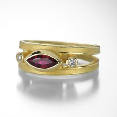 An 18k yellow gold split shank ring with a marquis shaped ruby (0.55cttw) and two round side diamonds (0.08cttw). Size 6.75.