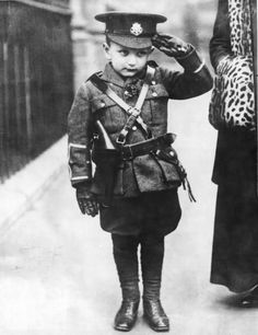 """A young man saluting in his own miniature copy of a WWI British army uniform."""
