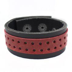 Bracelete em Couro Natural preto com 01 faixa sobreposta perfurada de couro na cor vermelha. A peça tem 02 botões reguladores de pressão em metal.