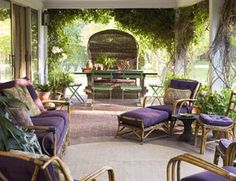Matching Sunbrella upholstery and a round indoor-outdoor rug from Couristan unify an assortment of vintage rattan porch furniture into an open-air living room suite. Behind the chaise longue, a grand hooded basket chair — handed down and restored for generations — presides over a massive table and lightweight French park chairs.