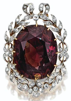 A Belle Époque alexandrite and diamond pendant-brooch, circa 1910. The cushion-shaped alexandrite weighing approximately 65.00 carats, within a floral and foliate wreath border set with small old European-cut and single-cut diamonds, mounted in gold and platinum.♥♥