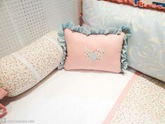 Almofada decorativa rosa e azul com passarinho em estampa floral para berço.