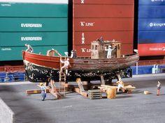Auf dem Kai, an dem ein großes Containerschiff angelegt hat, wird ein altes Fischerboot in mühevoller Handarbeit von der alten Farbe befreit und neu gestrichen.