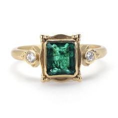 This one-of-a-kind ring features an enchanting emerald center gem accented by round, brilliant diamonds. This especially unique style blends vintage and modern aesthetics, and is handcrafted from satin finish yellow gold.