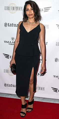 FREIDA PINTO | in a black midi with an ultra-high slit and Stuart Weitzman slide heels at the premiere of Blunt Force Trauma in L.A.