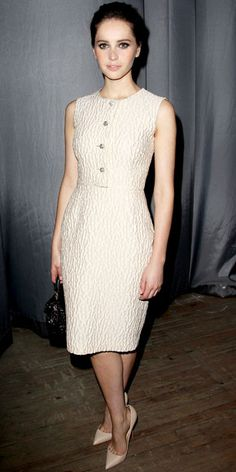 Felicity Jones viewed The Ever Changing Face of Beauty installation in a textured LWD, woven leather bag and nude Luboutins.