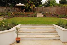 The combination of rendered walls, wide steps, warm stone copings and nice planting is very nice.  A white render and darker brown or grey stone would look good in the cottage - a more refined version of what you currently have.