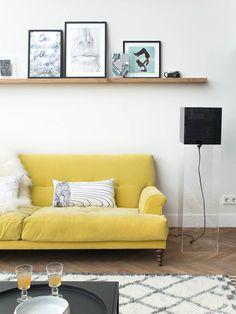 Salón con sofá en color amarillo y baldas en la pared con cuadros