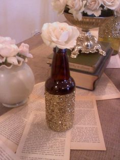 "colin wanted beer bottles as part of the centerpieces; i didn't. i wanted tons of glitter on the tables; he didn't. then our friend and her husband came up with a compromise. gold glitter beer bottles! i threw this together this morning. literally takes a few minutes, looks perfect with our overall ""rustic"" theme, and only requires one flower. it's something we both wanted, it's easy to recreate, and it saves us a ton of money since it is all supplies we alrea"