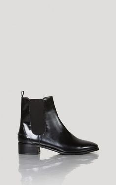 Fitted Chelsea boot in shiny black. Elastic side panels on inner and outer foot…