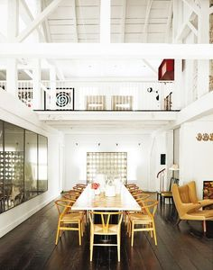 Contemporary dinning room with large dinning table, wooden chairs, and high ceilings