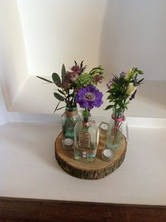 Tree truck with various glass bottles filled with seasonal favs such as roses, scabious, mint, Veronica