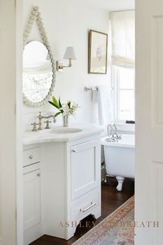 ASHLEY GILBREATH INTERIOR DESIGN: We love the clean white vanity and marble top, and the footed bathtub contrasted against dark wood floors. A beaded mirror adds a bit of whimsy to this otherwise sophisticated bathroom. Ashley Gilbreath, Feminine Bathroom, Casual Elegant Style, Beaded Mirror, Dark Wood Floors, White Vanity, Marble Top, Bathtub, Flooring
