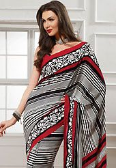 Style and trend will be at the peak of your beauty when you adorn this saree. This off white, black and red georgette saree is nicely designed with floral and stripe print work. Saree gives you a singular and dissimilar look. Matching red blouse is available. Slight color variations are possible due to differing screen and photograph resolution.