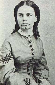 "first white women in U.S. was tattooed by Indians after be captured by Indians. The tattoo is called ""dirty mouth"" meaning she slept around    name Olive Oatman, 1858. After her family was killed by Yavapais Indians, on a trip West in the eighteen-fifties, she was adopted and raised by Mohave Indians, who gave her a traditional tribal tattoo. When she was ransomed back, at age nineteen, she became a celebrity. Photograph courtesy of the Arizona Historical Society, Tucson, 1927."
