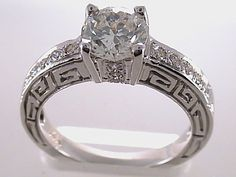 Stunning 14-kt. white gold engagement ring with round brilliant-cut center stone and pavé-encrusted band accented with Greek Key design from Sun Jewelry in Los Angeles, California....