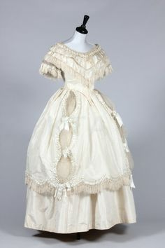 (Evening Bodice) Ivory and pale blue silk taffeta bridal gown and accessories worn by Henrietta Cordery for her wedding on June 27, 1857, comprising: day bodice with glass buttons coiled with metal snakes, short sleeved evening bodice trimmed with pale blue ribbon ruffles and fringes, similarly trimmed over-skirt and plain silk underskirt. Although a snake motif might seem an unusual adornment for a bridal gown, in the 19th century it was thought to symbolize wisdom and eternity.