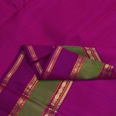 A thread work checkered pattern adorns the gorgeous fuchsia body. Th purple pallu is adorned by bands of zari and seepu rekku motifs. Bands of purple and moss green embellished with rudrakshas, bhuttas, neli and floral motifs in zari and thread work border the sari on either side. view more details at http://www.parisera.com/products/kanakavalli-handwoven-kanjivaram-silk-sari-100100511