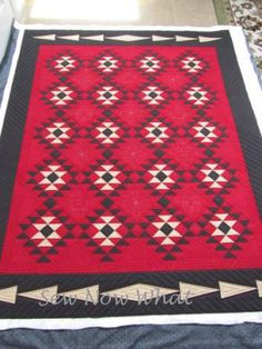 KAH says: looks like a rug, but it's actually a quilt. Great southwest design in red/cream/black.