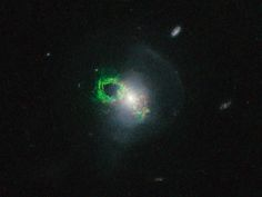 Click to Enlarge    This new NASA/ESA Hubble Space Telescope image shows ghostly green filaments, lying within the galaxy Teacup (also known as 2MASX J14302986+1339117). This filament was illuminated by a blast of radiation from a quasar — a very luminous and compact region that surrounds the supermassive black hole at the center of its host galaxy. Its bright green hue is a result of ionized oxygen, which glows brightly at green wavelengths.