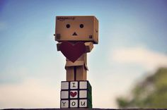 Amazon Box Guy holding a red heart while standing on a rubiks cube that just says I love you !