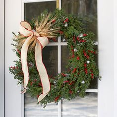 A spray of wheat stalks bound by ribbon adds rustic refinement to a boxwood wreath. Artificial winter berries brighten it up, and silver bells bring some jingle. #christmas #holiday #wreath
