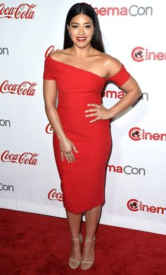 Gina Rodriguez is wearing a red Haney off shoulder fitted dress. Beautiful dress! Gina is elegant in this dress! It fits her beautifully.