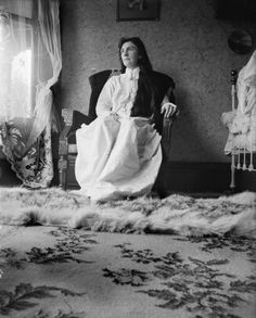 "Low angle view of ""Ma"" sitting in a large chair near a window wearing a long white dress or nightgown in a bedroom with a fur rug over another rug. There are framed pictures on the wall and a bed on the right.    For more information about this image,  1"