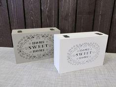 Puinen laatikko, väreinä harmaa tai valkoinen. Sisällä 6 lokeroa. Kannessa reikäkuvioitu teksti: Home sweet home. Edessä teksti: Tea.