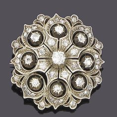 A late 19th century diamond brooch, circa 1880 The circular pierced plaque set with old brilliant and rose-cut diamonds, mounted in silver and gold, old brilliant-cut diamonds